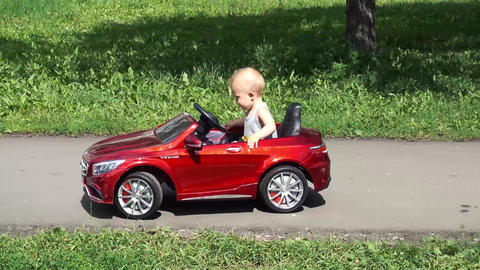 Baby boy is riding a toy car driven by father Footage