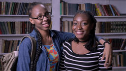 Two young african american women hugging in library and looking at camera, happy Footage