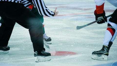 slow motion on-ice official throws puck on circle players wait Footage