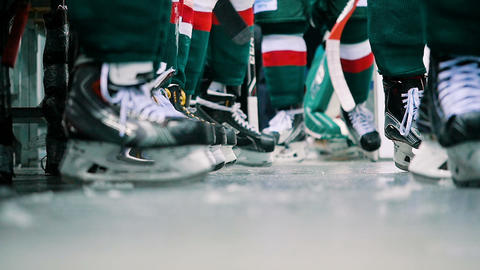 slow motion view under bench players feet in hockey skates Live Action