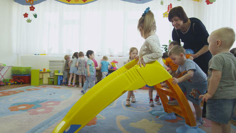 toddlers play on small plastic slide in kindergarten Footage
