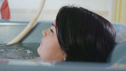 brunette woman lies in bath during underwater massage ビデオ