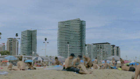 Sitting On The Beach Next to Big Highrises Footage