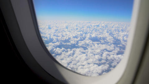 Fluffy cloudscape viewed from moving airplane window, itchy feet, wanderlust Live Action