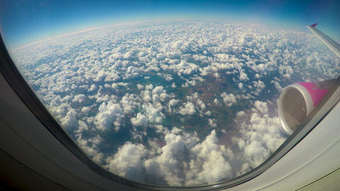 Fluffy clouds viewed from airplane windows, wing and turbine in shot, low cost Footage
