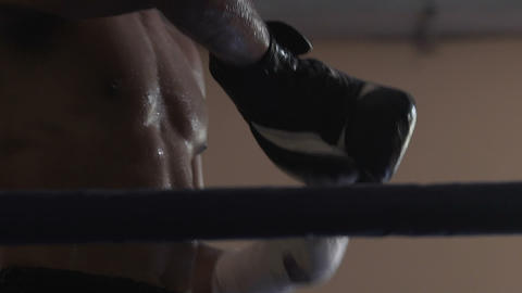 Exhausted and aggressive winner taking off boxing gloves after competition Footage