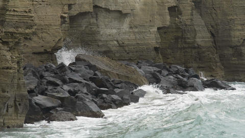Powerful waves hitting rocky cliffs and falling to produce froth and splashes Live Action