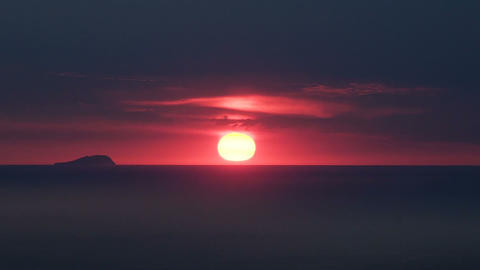 Dark red burning sky with sun hiding down over horizon, darkness falls, sunset Footage