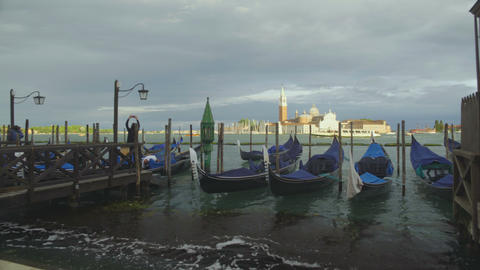 Gondolas rocking on waves of Grand Canal, tourist attraction in Venice, Italy Live Action