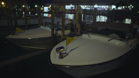 Taxi boats moored to pier rocking on canal waves, waiting for clients at night Footage