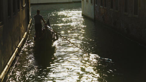 Silhouette of gondolier steering boat in Venice street, sun reflection in water Footage