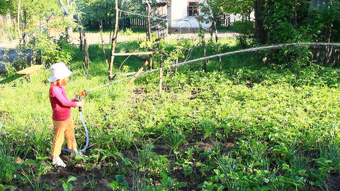Little girl is watering garden and bed. Orchard irrigation ビデオ