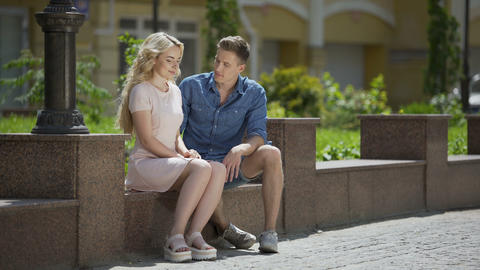 Couple sitting on bench guy, hugging shy girl at first date, romantic mood Live Action