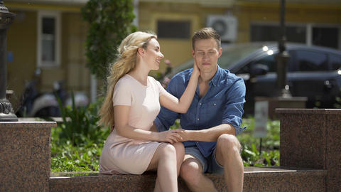Girlfriend and boyfriend sitting on bench holding hands, talking, relationship Live Action