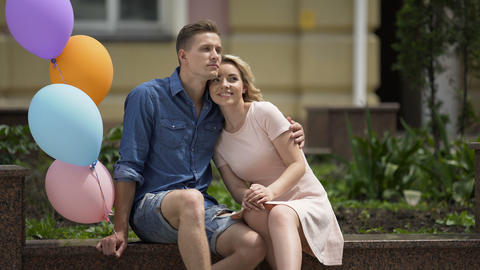 People in love sitting on bench, guy holding balloons,... Stock Video Footage