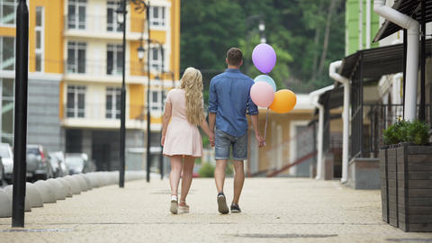 Young couple walking down street holding hands, guy holding balloons, romantic Live Action