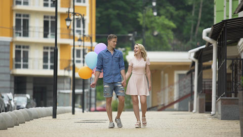 Male with balloons and female strolling down street and talking, romantic date Live Action