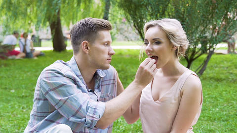 Happy couple eating sweets together, feeding each other and laughing, happiness Footage