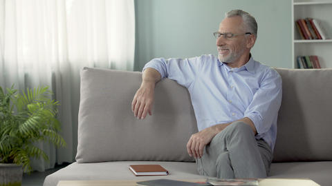 Happy mature male sitting on couch and remembering last summer vacation Footage