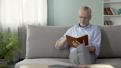 Happy old man sitting on couch and reading interesting book, hobby and free time Footage