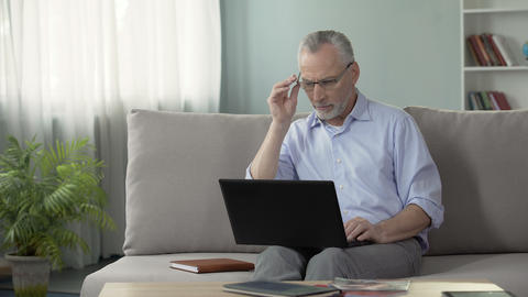 Male in his 50s sitting on couch and working on laptop, freelance and profession Live Action
