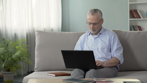 Healthy senior male sitting on sofa and viewing photos on dating website, laptop Live Action