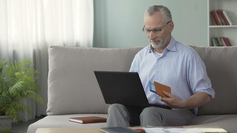 Satisfied old man booking hotel room on laptop, holding passport and tickets Footage