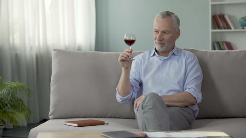 Pleased senior male sitting on couch and enjoying perfect flavor of red wine Live Action