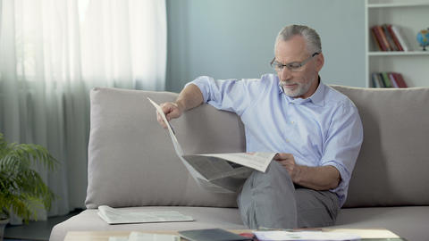 Old male sitting on sofa and reading newspaper, press and news, rest time Footage