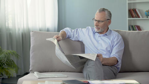 Senior male sitting on couch and reading newspaper, morning ritual, press Footage