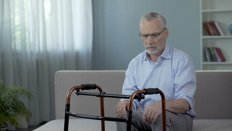 Old male sitting on couch and looking at walking frame standing in front of him Footage