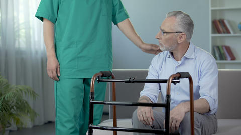 Old depressed male sitting on couch and looking on walking frame, nursing home Footage