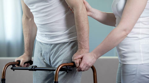 Caring wife helping ill husband to move with walking frame, rehabilitation Footage
