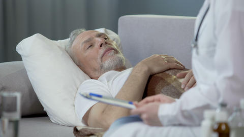 Retired man lying in bed and chatting with physician, healthcare and medicine Live Action