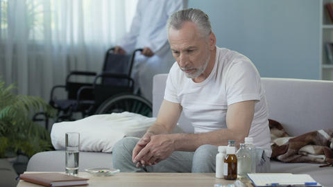 Old person sitting on couch and looking at pills, male nurse bringing wheelchair Footage