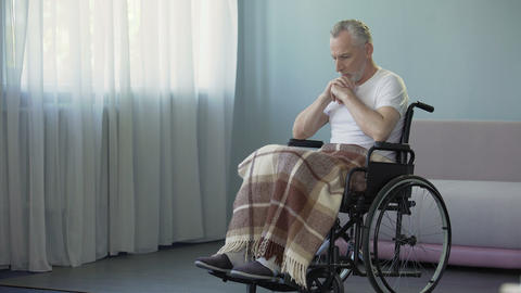 Handicapped pensioner sitting in wheelchair and thinking about life, sadness Footage