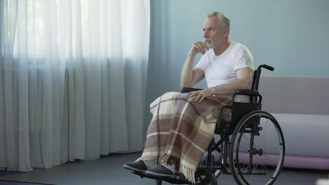 Male pensioner sitting in wheelchair and waiting for his family at nursing home Footage