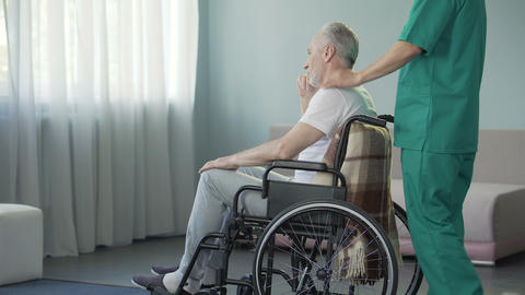 Heedful male nurse taking old man with disabilities to procedures, taking care Live Action