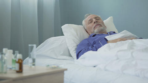 Weak male patient drowsing on hospital bed after taking daily dose of medication Live Action