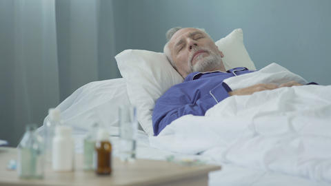 Sick man taking dose of medicines and having rest, lying in bed, daytime sleep Live Action