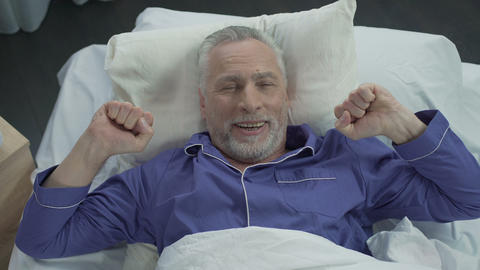 Elder basking in his bed rejoicing at new orthopedic mattress, comfortable sleep Footage