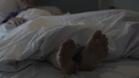 Sleeping man scratching his feet, nasty smell and discomfort due to foot fungus Footage