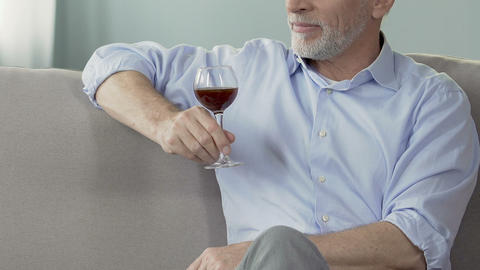 Elderly man sitting on sofa with glass of wine, enjoying moment, private winery Footage
