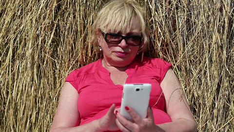 Blonde woman sits near haystack and uses smartphone Footage