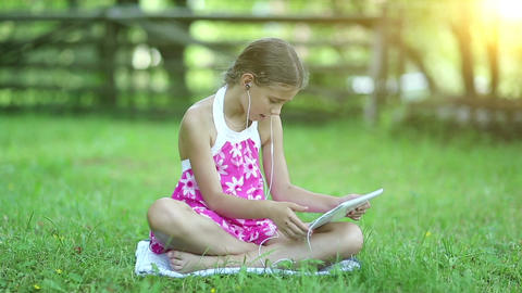 Beautiful girl with tablet computer sits on the grass in garden at sunset Footage
