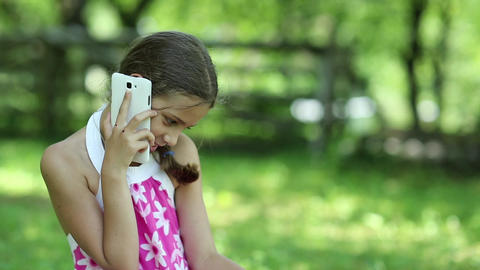 Beautiful girl sits on the grass and talks on the cell phone Footage