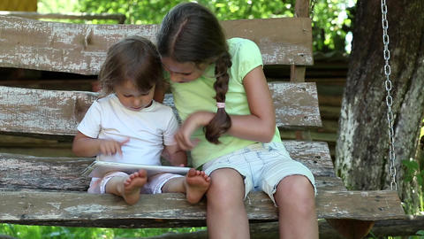 Two sisters with tablet PC sits on the swing bench Footage