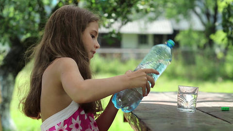 Pretty girl pours water from bottle into a glass Footage