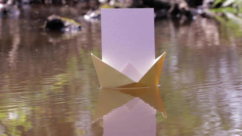 Paper boat floating on the waters of a shallow over flying insects 75 Footage