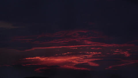 Red clouds flowing over remember illuminated by the last rays of the sun 38 Footage